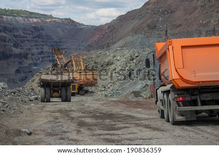 Heavy mining trucks being loaded with iron ore on the opencast