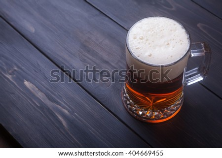 Heavy mug with amber beer on a dark wooden surface - stock photo