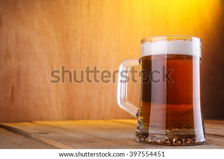 Heavy mug with light beer on a grunge wood surface - stock photo