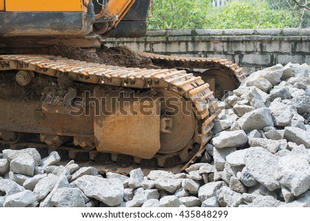 heavy organge excavator with shovel standing on hill with rocks - stock photo
