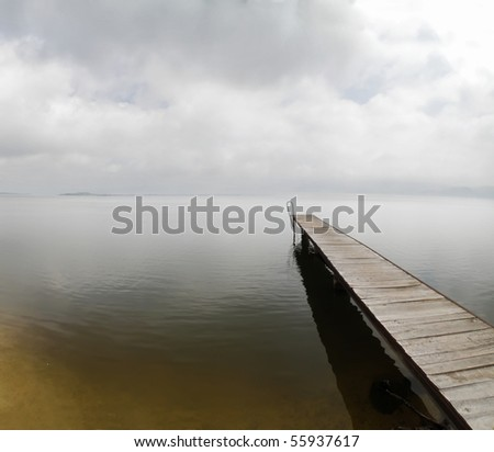 heavy overcast sky over empty pier on misty river Danube - stock photo