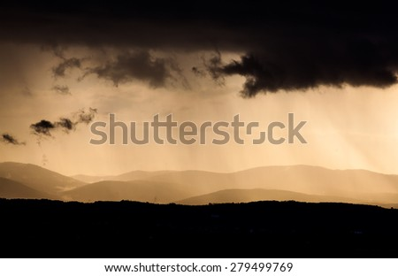 Heavy pink and grey clouds with light rain showers - stock photo
