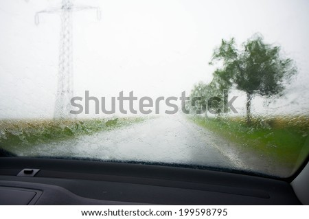 heavy rain from inside the car in the summer on the road - stock photo