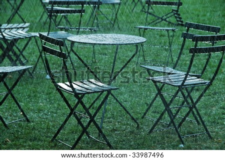 Heavy rain splashing on table & chairs - stock photo