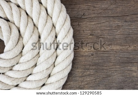 Heavy rope on weathered wooden background. - stock photo