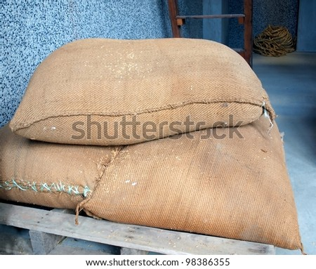 Heavy sacks with rice that is prepared to be hulled - stock photo