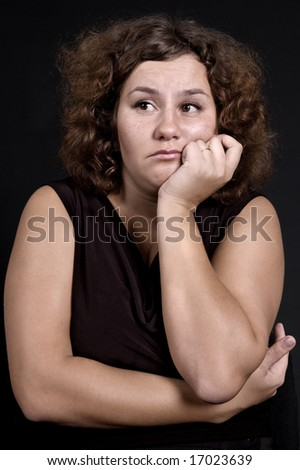 heavy sad woman against dark background - stock photo
