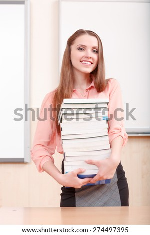 Heavy science. Attractive young girl standing and holding pile of books on background of white blackboard - stock photo