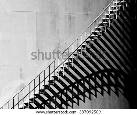 Heavy shadow of stairway on old white storage tank. Stairs cast interesting shadows in the late afternoon Sunlight. Black and White - stock photo