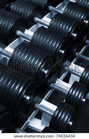 Heavy sports dumbbells in modern sports club - stock photo