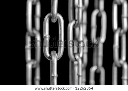 Heavy stainless steel chains on black.  Focus n the chain in the forefront. - stock photo