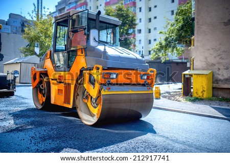 Heavy tandem Vibratory roller compactor working on asphalt pavement at road repairing - stock photo