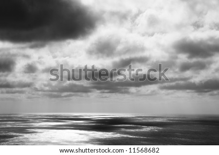 heavy thunderstorm with dark clouds over the ocean - stock photo