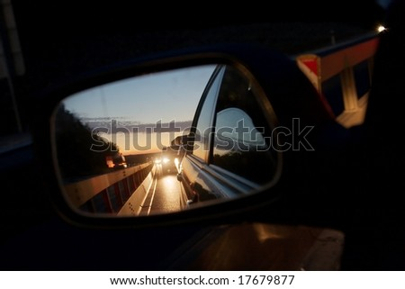 Heavy traffic at night reflecting in the sideview mirror of a car - stock photo