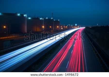 Heavy traffic on a highway. Due to the long exposure time the front and rear lamps of the cars are forming a white and a red snake of light. There are huge storage tanks on the left side. - stock photo