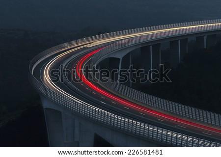 Heavy traffic on the modern bridge. Light trails. Transportation. Blurs - stock photo