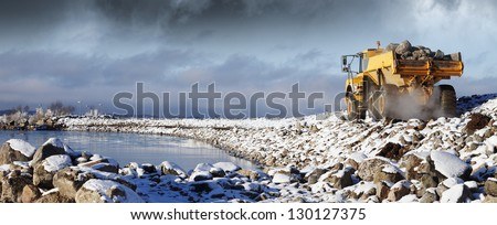 heavy truck driving in rough snowy terrain - stock photo