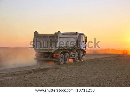 Heavy truck in dusty sunset - stock photo