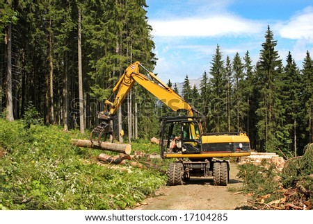 Heavy truck lifting logs - stock photo