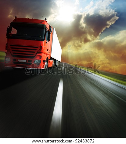 Heavy truck on blurry asphalt road under sunlight - stock photo