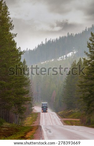 Heavy truck on narrow road in forest area on rainy spring day in sweden