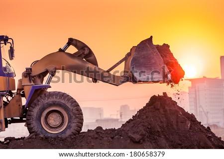 heavy wheel excavator machine working at sunset - stock photo