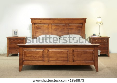 Heavy wood queen-size bed set with headboard and bedside table drawers - stock photo