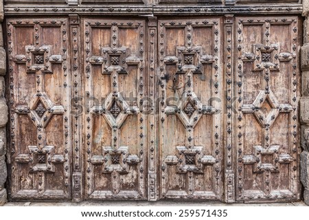 Heavy wooden doors with relief carved patterns - stock photo