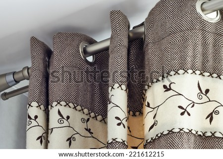 heavy woolen  braun curtains  with ring-top rail - stock photo