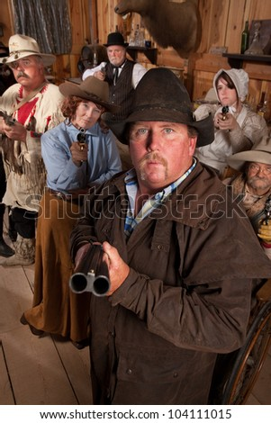 Heavyset gunslinger with shotgun in crowded old western saloon