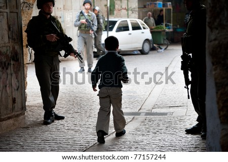 HEBRON, OCCUPIED PALESTINIAN TERRITORIES - APRIL 6: A Palestinian child passes through the midst of an Israeli military patrol in Hebron's old city on April 6, 2011.
