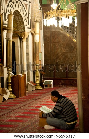 HEBRON, OCCUPIED PALESTINIAN TERRITORIES - FEBRUARY 26: An unidentified worshiper studies the Koran in the Al-Ibrahimi Mosque in the West Bank city of Hebron, Occupied Palestinian Territories on Feb. 26, 2012. - stock photo