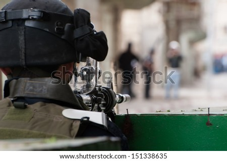 HEBRON, PALESTINIAN TERRITORY - FEBRUARY 22: An Israeli soldier aims an assault rifle at Palestinians during a protest against the Israeli occupation in the West Bank city of Hebron, February 22, 2013 - stock photo