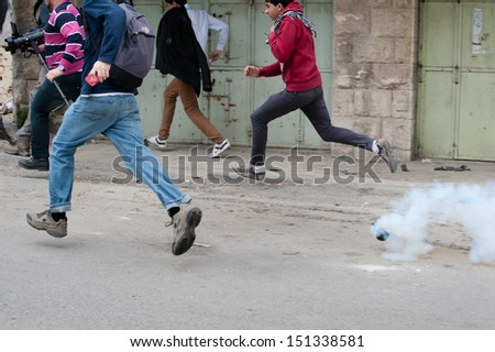 HEBRON, PALESTINIAN TERRITORY - FEBRUARY 22: Demonstrators flee tear gas launched by Israeli forces during a protest against the Israeli occupation in the West Bank city of Hebron, February 22, 2013. - stock photo