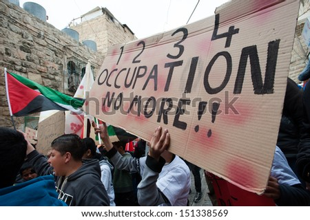 HEBRON, PALESTINIAN TERRITORY - FEBRUARY 22: Palestinians march during a protest against the Israeli occupation in the West Bank city of Hebron, February 22, 2013.  - stock photo
