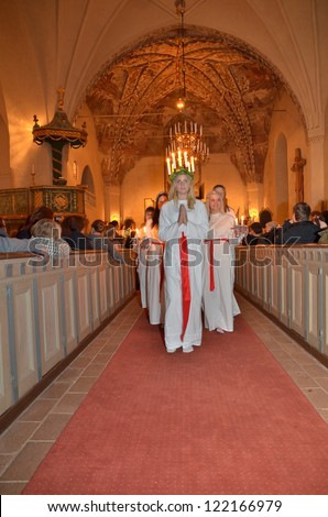 HEBY, SWEDEN - DECEMBER 16:unidentified people in Santa Lucia at christmas celebration in Heby church on December 16, 2012 in Heby Sweden - stock photo