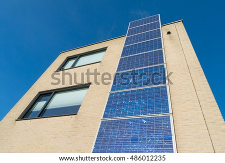 HEERHUGOWAARD, NETHERLANDS - JANUARY 23, 2016: modern house in the netherlands with a row of solar panels at its facade