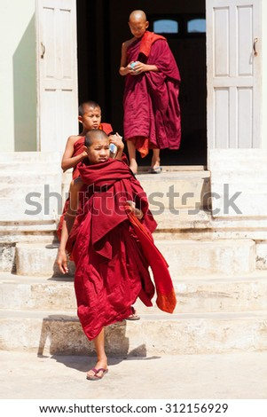 Heho, Myanmar - March 01, 2011 : Young monks in red robes walking in the streets