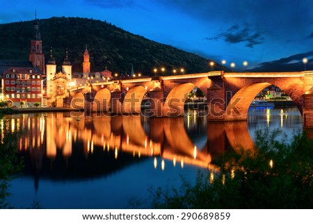 Heidelberg, Germany, the Old Bridge at twilight reflected in the water of the Neckar river - stock photo
