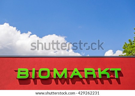 "Heidenheim, Germany - May 26, 2016: Organic food market / bio market, red facade labeled with ""BIOMARKT"", german language, blue sky with clouds"