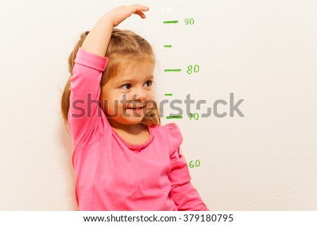 Height measurement by little girl at the wall - stock photo