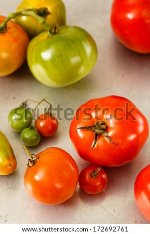 Heirloom tomatoes rest on an old, worn metal baking sheet. - stock photo