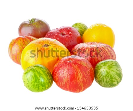 Heirloom tomatoes with water drops on white background - stock photo