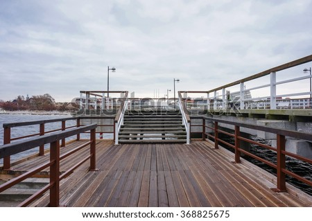 HEL, POLAND - NOVEMBER 13, 2015: Wooden platform and stairs of a pier on a cloudy day - stock photo