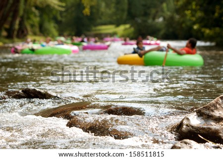 HELEN, GA - AUGUST 24:  De-focused people enjoy tubing down the Chattahoochee River in North Georgia on a summer afternoon, as boulders in foreground are in focus, on August 24, 2013 in Helen, GA.  - stock photo