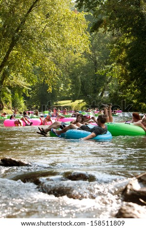 HELEN, GA - AUGUST 24:  Dozens of people relax while tubing down the Chattahoochee River in North Georgia on a summer afternoon, on August 24, 2013 in Helen, GA.  Hundreds went tubing down the river. - stock photo