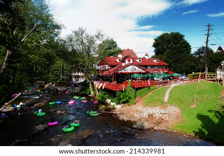 Helen, GA, USA - Aug. 31 2014: Tourists having fun tubing in Chattahoochee river passing restaurant cafe in Alpine Helen, GA. - stock photo