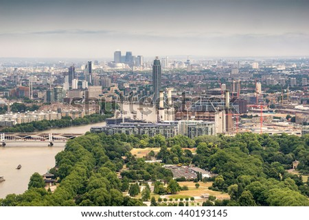 Helicopter aerial view of London with Thames and Canary Wharf on background.