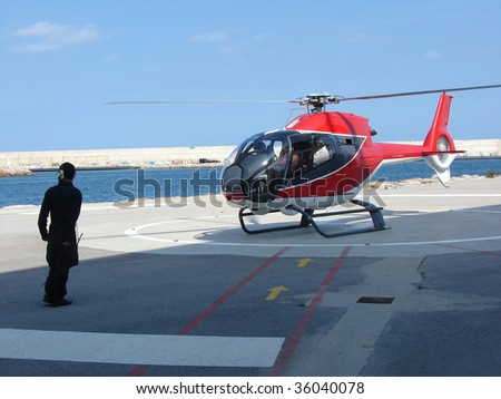 helicopter and the mechanic on a take-off platform - stock photo