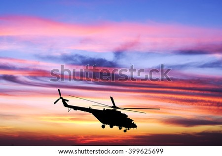 Helicopter at sunset in the sky - stock photo